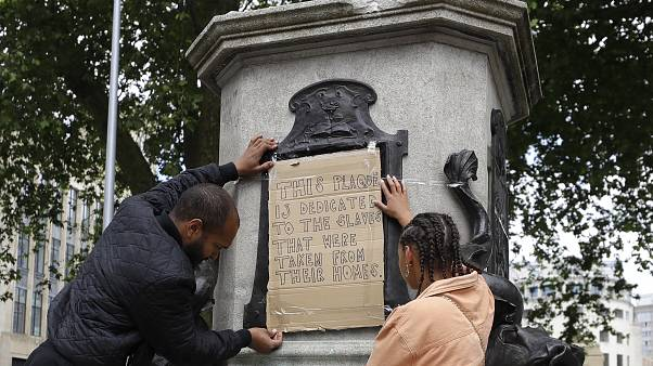 A banner is taped over the inscription on the pedestal of the toppled statue of Edward Colston in Bristol, England, Monday, June 8, 2020