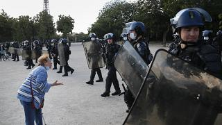 An elderly woman haggles French riot police during a demonstration in Paris, France, Saturday, June 6, 2020, to protest against the recent killing of George Floyd.