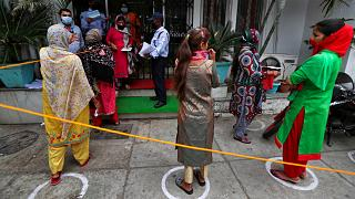 Indians queue up outside a bank to withdraw money during lockdown in Jammu, India, Tuesday, April 7, 2020.