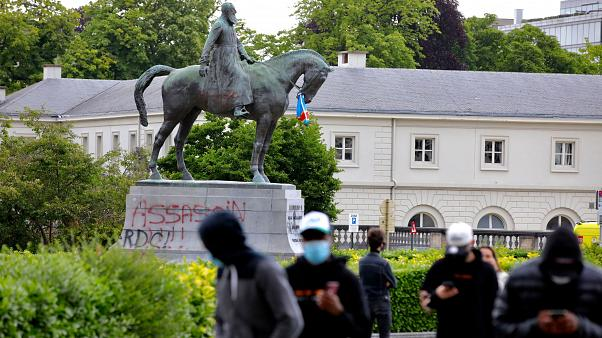 A statue of Belgium's King Leopold II is defaced with the words 'assassin' prior to a Black Lives Matter protest rally in Brussels