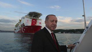 Turkey's President Recep Tayyip Erdogan, pose for photographs, backdropped by 'Fatih'