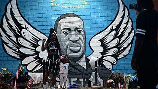 أناس يقفون أمام صورة حائطية لجورج فلويد في هيوستن، تكساس - 2020/06/08