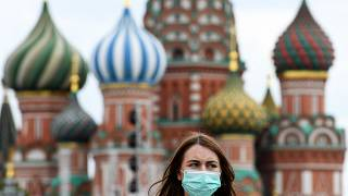 A woman wearing a protective face mask walks in front of the Saint Basil's Cathedral during the annual book fair on the Red Square in downtown Moscow on June 6, 2020
