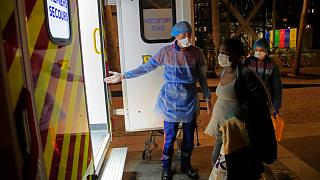 First aiders escort a pregnant woman suspected of coronavirus infection infection to an ambulance in Paris, Thursday, March 26, 2020.