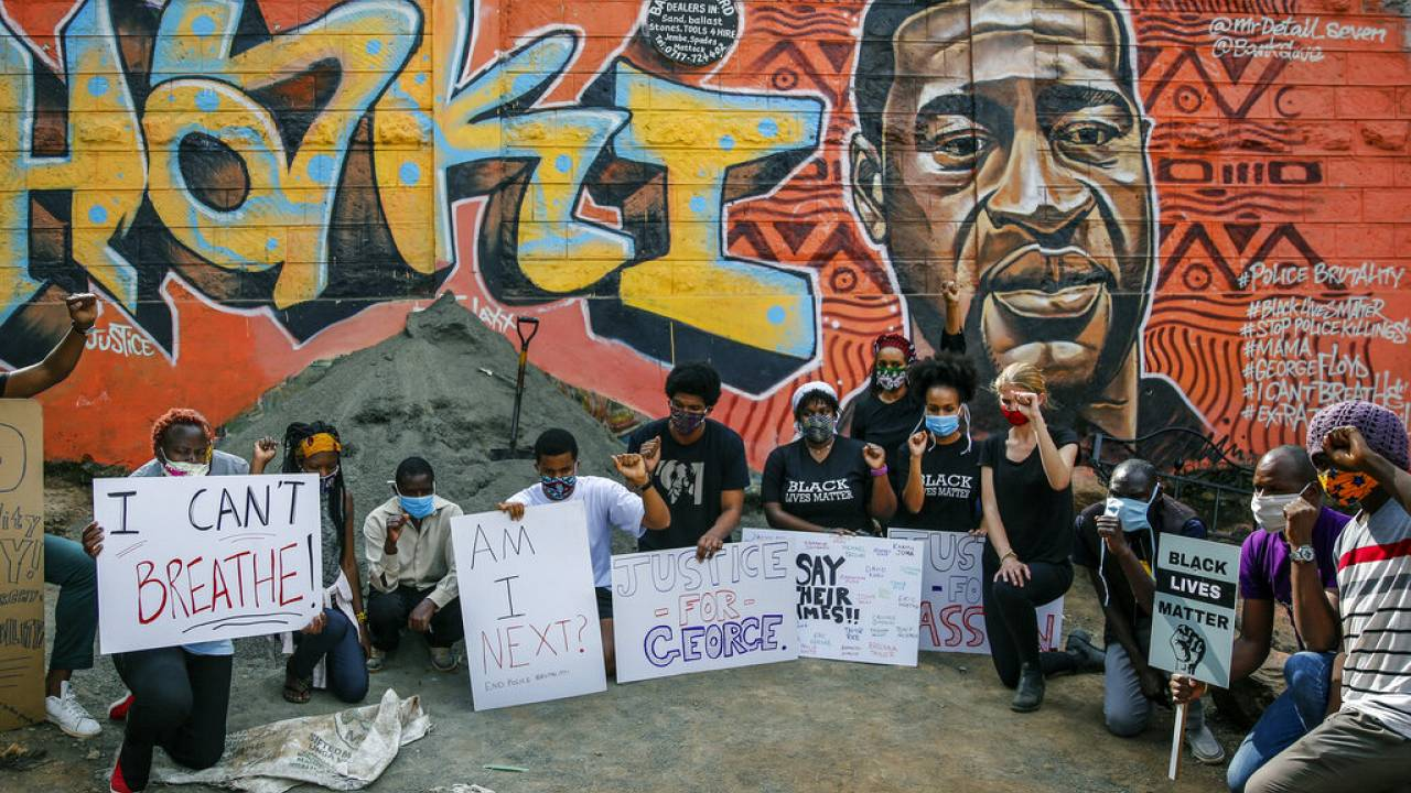 """Protesters against police violence gather next to a new mural painted this week showing George Floyd with the Swahili word """"Haki"""" meaning """"Justice""""."""