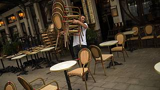 A waiter sets up a restaurant terrace during the partial lifting of coronavirus COVID-19 lockdown regulations in Brussels, June 8, 2020. (AP Photo/Francisco Seco)
