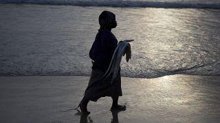 Une femme tient un poisson sur la plage de saint-Louis, Sénégal, le 18 mai 2013