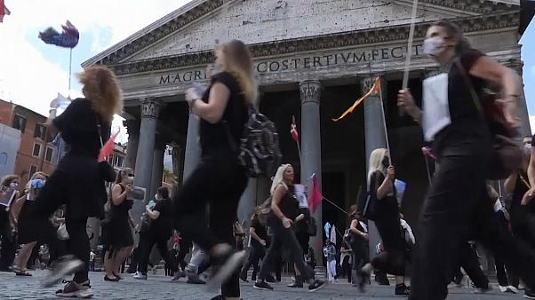 Tour Guide protesters dressed in black in front of the Pantheon, clapping hands and banging lids
