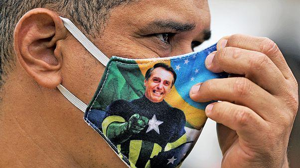 Brezilya Başkanı Jair Bolsonaro resimli maske takan bir kişi