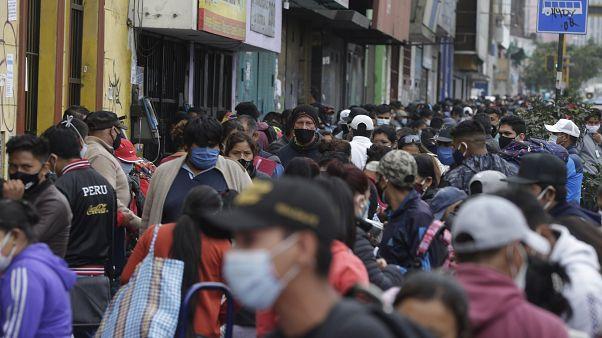 Cientos de personas, vendendores ambulantes, compradores y transeúntes, abarrotan una calle en Lima