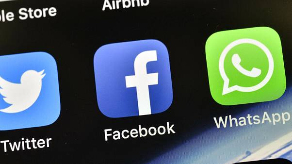 n this Nov. 15, 2018, file photo the icons of Facebook and WhatsApp are pictured on an iPhone in Gelsenkirchen, Germany.