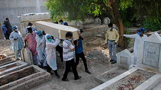 Rescue workers and family members carry the casket of Khursheed Bibi, who died due to coronavirus, for her burial at a cemetery in Hyderabad, Pakistan