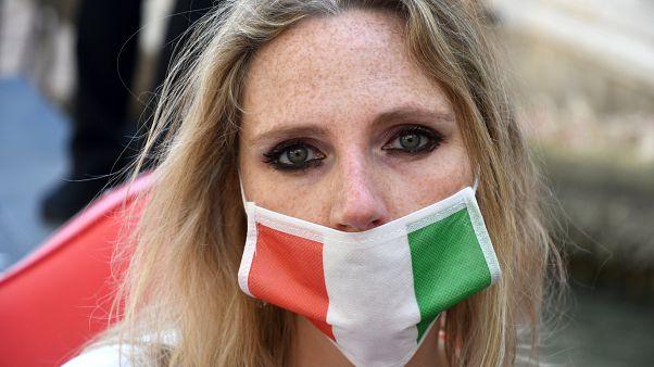 فتاة إيطالية تضع قناعا واقيا