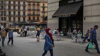 In this Monday, June 1, 2020 photo, people walk past a terrace bar with local customers in Barcelona downtown.