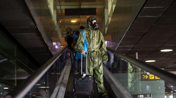 A passenger wearing a protective suit arrives from London at the Barcelona airport, Spain, on Friday, May 15, 2020.