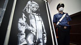 Csendőr őrzi a Banksy-művet az ügyészségi sajtóértekezleten, L'Aquilában