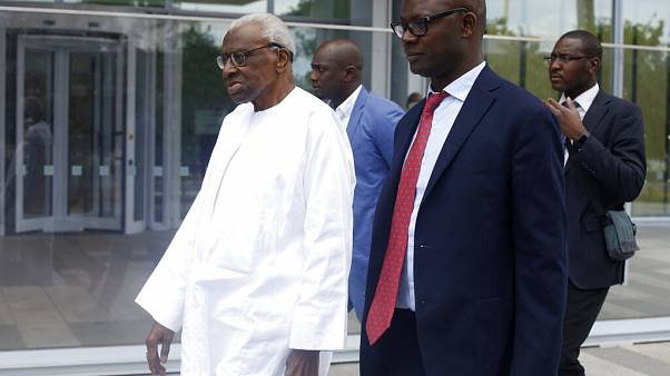 Former president of the IAAF (International Association of Athletics Federations) Lamine Diack, left, arrives at the Paris courthouse, Wednesday, June 10, 2020