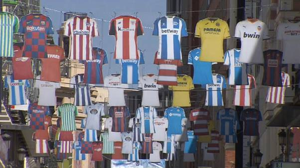 Jerseys of Spanish top tier football clubs hang over Preciados Street, a popular shopping street in Madrid