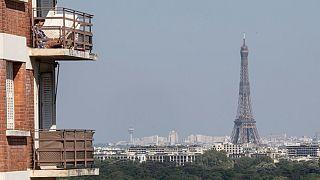Una donna si gode il sole sul balcone, mentre la Torre Eiffel è chiaramente visibile sullo sfondo. L'inquinamento atmosferico è diminuito a Parigi, durante il confinamento