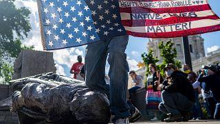Un Amérindien Lakota presse symboliquement son genou sur la statue de Christophe Colomb à Saint Paul - capitale du Minnesota - le 10 juin 2020