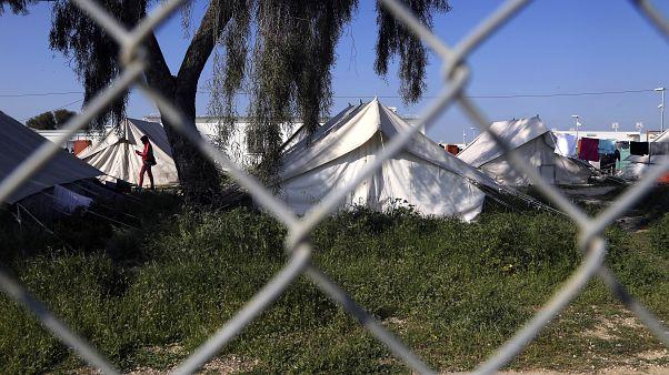 مهاجرٌ يسير قرب الخيام داخل مخيم للاجئين في كوكينوتريميثيا قرب العاصمة القبرصية، نيقوسيا