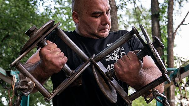 A man trains in the outdoor gym on Dolobetskyi island in the Dnieper River in Kyiv, Ukraine