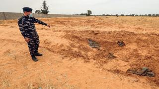 A member of security forces affiliated with the Libyan Government of National Accord (GNA)'s Interior Ministry points at the reported site of a mass grave in town Tarhuna