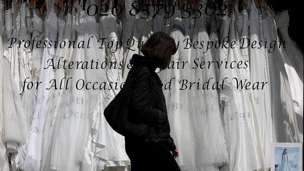 woman walks past a Wedding dress shop in London, Tuesday, June 9, 2020, where bride dresses pile unused in the shop window.