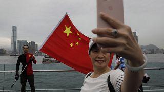 شخص يحمل العلم الصيني في هونغ كونغ