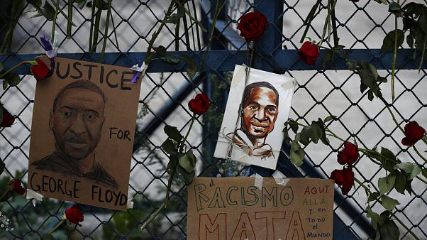 Images of George Floyd hang surrounded by roses on a security barrier outside the US embassy in Mexico City