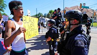 A protester and police face each other during a demonstration near a private event attended by President Donald Trump, Thursday, June 11, 2020.