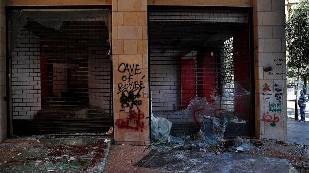 Un uomo guarda i negozi danneggiati durante una protesta antigovernativa a Beirut, Libano
