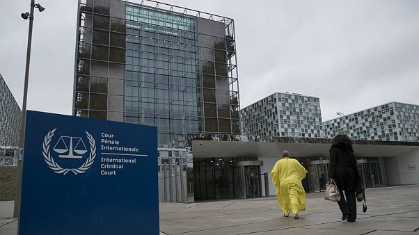 Supporters of former Ivory Coast President Laurent Gbagbo walk towards the International Criminal Court in The Hague, Netherlands, Wednesday, Jan. 16, 2019