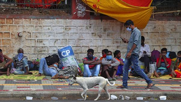 Migrant workers from other states rest on a pavement as they wait for trains to their home states in Hyderabad, India