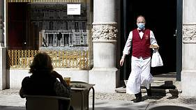 A waiter wearing a face mask brings an order to a customer sitting outdoor at the Versailles restaurant and pastry shop in Lisbon, Monday, May 18, 2020