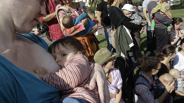 Mothers feed their children during the first day of the 6th World Breastfeeding Week
