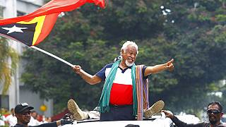East Timorese independence hero Xanana Gusmao, center, waves a national flag upon arrival in Dili, East Timor, Sunday, March 11, 2018