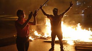 Anti-government protesters shout slogans as they block a highway with burning tires and wood, in downtown Beirut, Lebanon.