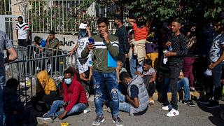 Migrants wait outside the Greek government's asylum service to submit documents for asylum claims, in Athens on Thursday, June 11, 2020.