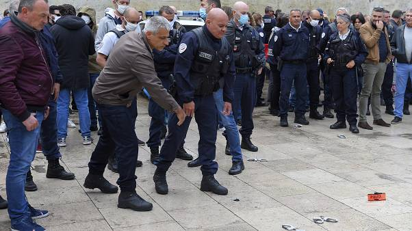French police throw handcuffs and arm band on the ground following demonstrations against police brutality and racism.