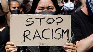 """Una donna mostra un cartello """"Stop al razzismo"""", durante a una manifestazione a Berlino (06/06/2020)"""