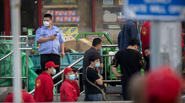 Police and security officials watch as workers line up outside a building holding a beef and lamb market in Beijing that was closed by authorities Friday, June 12, 2020