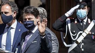 Italian Premier Giuseppe Conte, center, wears a face mask to prevent the spread of COVID-19 as he leaves after addressing parliament at the Senate, in Rome, May 21, 2020.