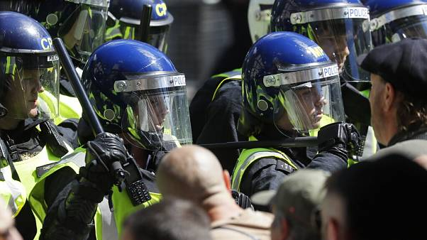 British police officers in riot gear scuffle with members of far-right groups protesting against a Black Lives Matter demonstration, in central London, Saturday, June 13, 2020