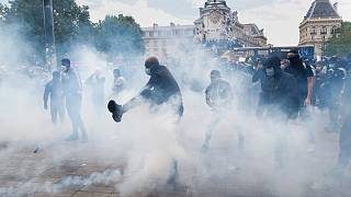 Un uomo dà un calcio a una bomboletta di gas lacrimogeno, durante la marcia contro la brutalità della polizia e il razzismo a Parigi, in Francia