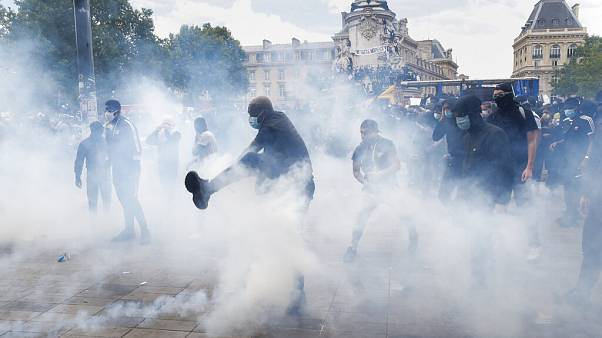 A man kicks a tear gas canister during a march against police brutality and racism in Paris, France, Saturday, June 13, 2020