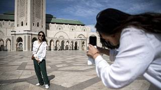 سائحة تلتقط صورة في مسجد الحسن الثاني في الدار البيضاء