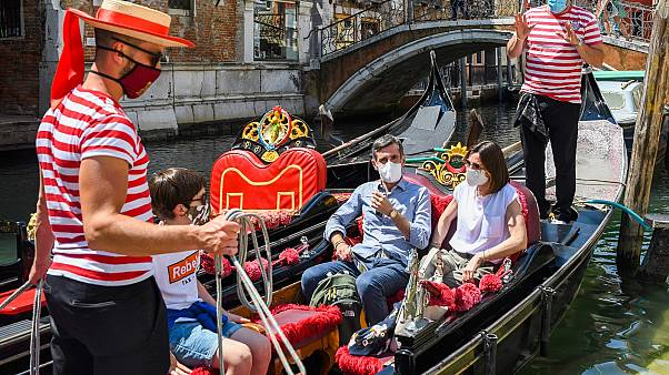 Gondoliers go with customers for a gondola ride on a canal in Venice on June 12, 2020