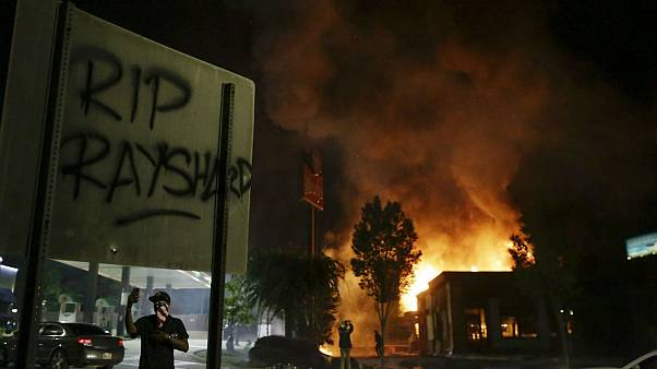"""RIP Rayshard"" is spray painted on a sign as as flames engulf a Wendy's restaurant during protests in Atlanta"