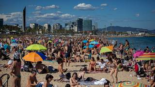 People enjoy the warm weather on the beach in Barcelona, Spain
